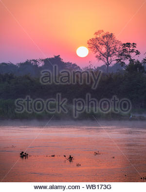 Beautiful sunset in the Cuiaba River, in the brazilian Pantanal wetlands. - Stock Photo