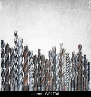 Old rusty drill bits of different sizes isolated on gray grunge background with copy space on top, construction background - Stock Photo