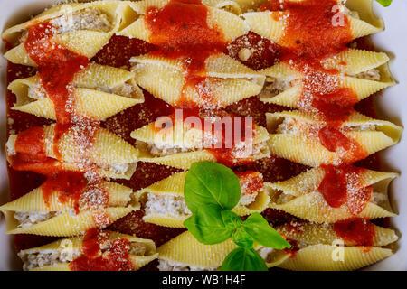 Jumbo shells pasta stuffed with meat, ricotta, tomato sauce. Closeup. - Stock Photo