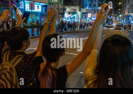 "Hong Kong protesters of different ages hold hands across the road in a busy local residential area to form human chain to call for democracy. They would retreat back to the pavement when the traffic light for the pedestrians turns red to let the traffic pass.Thousands of Hong Kong protesters link hands to form human chain across the city to call for democracy. The chains, which traced three subway routes, totaled around 40 kilometers (25 miles) in length. The protesters said they were inspired by the ""Baltic Way', when millions created a chain across three countries (Estonia, Latvia and Lithua - Stock Photo"