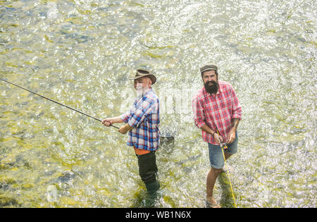 Active sunny day. Fishermen fishing equipment. Hobby sport activity. Fishermen friends stand in river. Fish normally caught in wild. Summer leisure. Men bearded fishermen. Weekends made for fishing. - Stock Photo