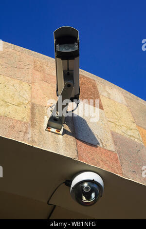 CCTV camera mounted on an exterior wall of a building, against a blue sky. - Stock Photo