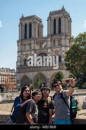 PARIS, FRANCE:  Tourist family taking selfie in front of Notre-Dame Cathedral before the fire in 2019 Stock Photo