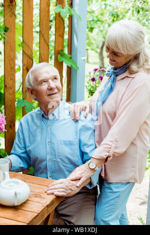 cheerful senior woman standing near happy husband holding cup - Stock Photo