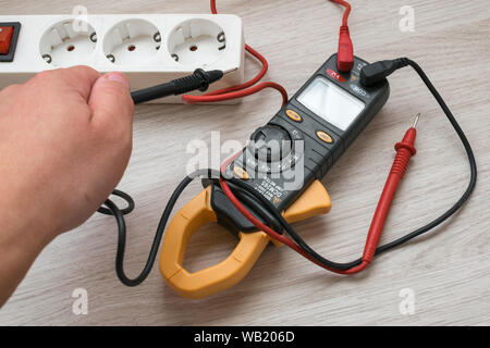 Hand using a digital clamp meter - Stock Photo