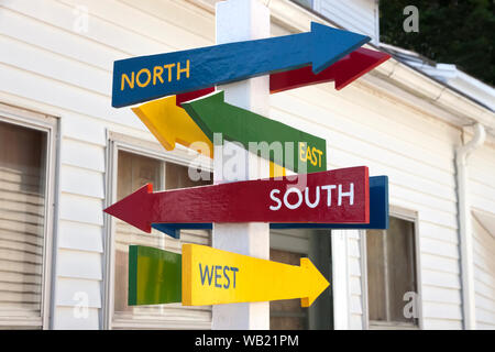 Signs with North, South, East, and West arrows pointing in different directions. - Stock Photo