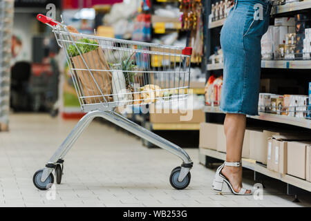 cropped view of woman standing near shopping cart with groceries in store Stock Photo