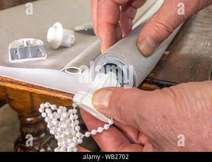 Close shot of a man's hands holding a new roller blind on a table, while pushing in a pulley with attached cord to one end of the metal tube. - Stock Photo