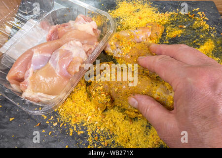 Close overhead shot of a man's hands coating pieces of raw chicken with a dry seasoning mix, ready for cooking. - Stock Photo