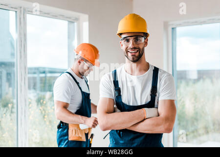 happy repairman in goggles standing with crossed arms near coworker - Stock Photo
