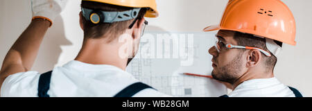 panoramic shot of architects in helmets looking at blueprint - Stock Photo