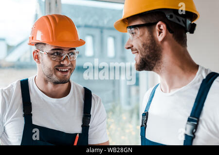 happy repairmen in helmets and goggles looking at each other - Stock Photo