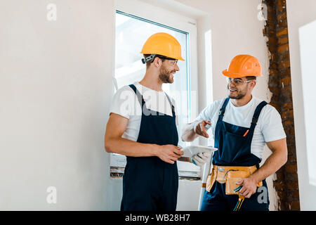 cheerful repairman in goggles looking at coworker while holding digital tablet - Stock Photo