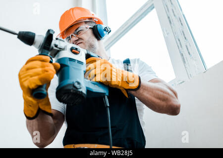 low angle view of handyman in helmet and yellow gloves using hammer drill - Stock Photo