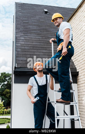 handsome man in uniform holding paper roll and looking at coworker standing on ladder - Stock Photo