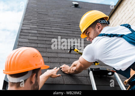 low angle view of repairman looking at coworker while holding hammer - Stock Photo