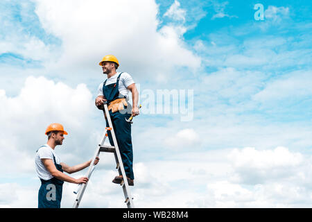 cheerful repairmen standing on ladder and smiling against blue sky with clouds - Stock Photo
