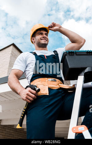 low angle view of happy repairman touching helmet while holding hammer - Stock Photo