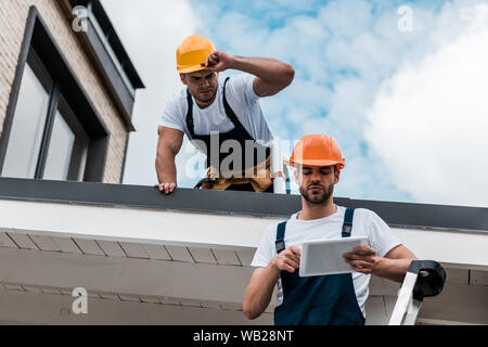 low angle view of man looking at coworker in helmet using digital tablet - Stock Photo