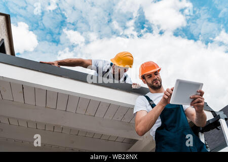low angle view of handsome handyman using digital tablet near coworker on roof - Stock Photo