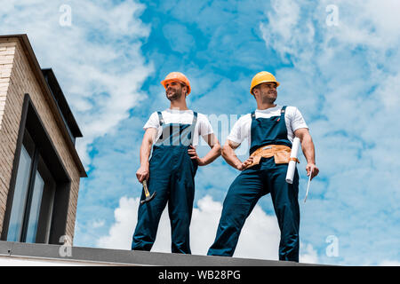 low angle view of handsome handymen standing with hands on hips - Stock Photo