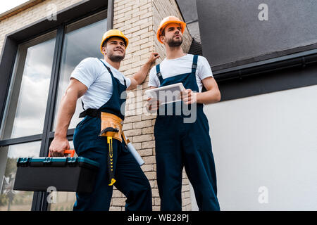 low angle view of handsome handyman holding toolbox near coworker with digital tablet - Stock Photo
