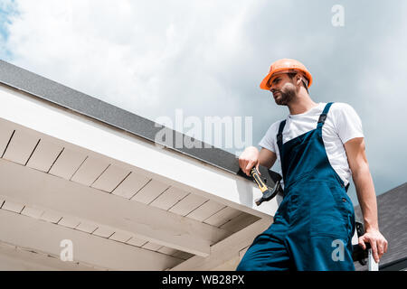 low angle view of repairman in helmet and uniform holding hammer and standing against blue sky with clouds - Stock Photo
