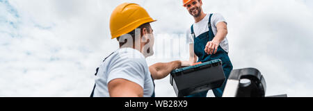 panoramic shot of handyman giving toolbox to happy colleague - Stock Photo
