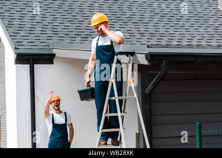 selective focus of cheerful handyman waving hand and looking at coworker talking on smartphone - Stock Photo