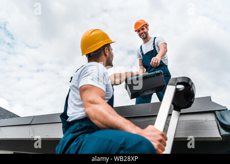 low angle view of handyman in helmet giving toolbox to happy colleague - Stock Photo