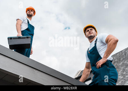 low angle view of handsome handymen in helmets against sky with clouds - Stock Photo