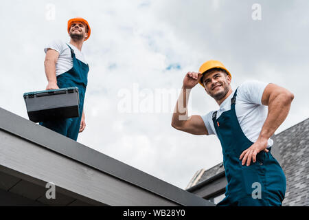 low angle view of happy handymen in helmets against sky with clouds - Stock Photo