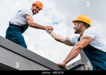 low angle view of cheerful handymen in helmets holding hands - Stock Photo
