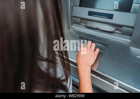 cropped view of woman entering pin code on atm machine - Stock Photo
