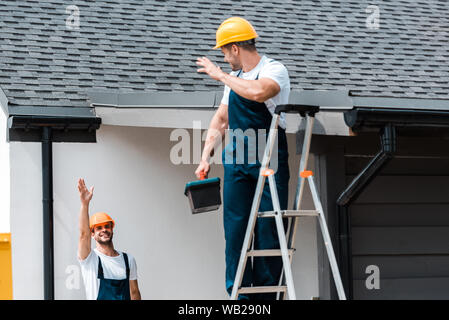 selective focus of workman waving hand and looking at coworker standing on ladder with toolbox - Stock Photo