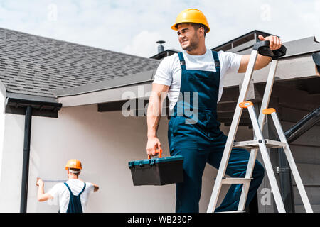 selective focus of happy workman standing on ladder with toolbox near coworker - Stock Photo