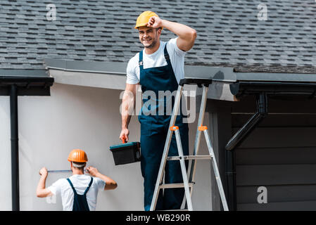 selective focus of happy repairman touching helmet and standing with toolbox on ladder near coworker - Stock Photo