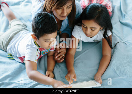 A family of a 9-year old girl, a 5-year old boy and their mother are lying on the bed. They're looking at a tablet. They're dressed with summer clothe