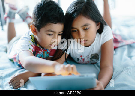 A 9-year old girl and a 5-year old boy are lying on the floor. They're looking at a tablet. They're dressed with summer clothes. It's daytime. They ha