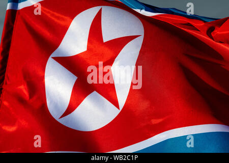 The national flag of the Democratic people's Republic of Korea flutters in a wind - Stock Photo
