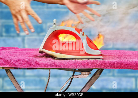 A clothes iron is connected to a power point located on an ironing board, it overheats and ignites, a person tries to grab a flame-clad iron and put o - Stock Photo