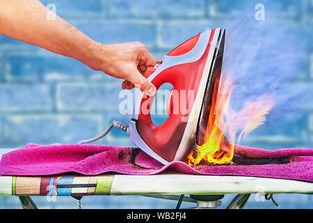 An overheated clothes iron ignited on an ironing board, a fire started in the house, a hand raises a charred iron. The plastic melted, the linen burne - Stock Photo