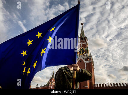 Russian soldier carries the flag of the European Union against the Spasskaya tower of the Moscow Kremlin on the Red Square in Moscow, Russia - Stock Photo