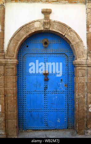 Typical, medieval Arabesque style, blue intricately carved, studded, Moroccan riad door and door-frame, Azemmour, El Jadida, Morocco. - Stock Photo