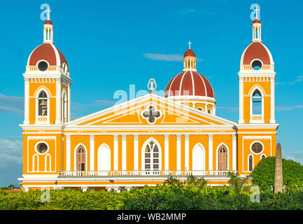 The facade of the neo-classical cathedral in yellow and orange tones at sunset in Granada, Nicaragua, Central America. - Stock Photo