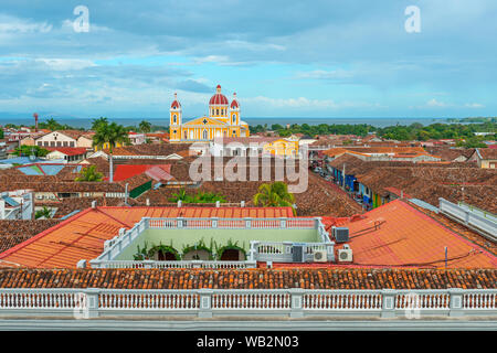Cityscape of Granada city with its colorful yellow cathedral, spanish colonial style architecture and the Nicaragua lake in the background, Nicaragua. - Stock Photo