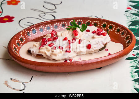 Chile en Nogada, a traditional dish from Puebla with the addition of walnut cream, pomegranate seeds and parsley. - Stock Photo