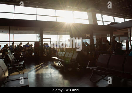 Passengers waiting in line for departure in an airport's waiting hall - Stock Photo