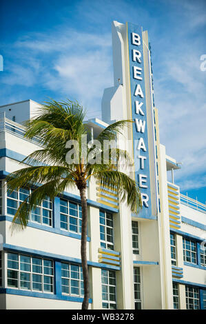 MIAMI - SEPTEMBER 15, 2018: A palm tree complements the Streamline Moderne architectural style of the Art Deco Breakwater Hotel on Ocean Drive. - Stock Photo