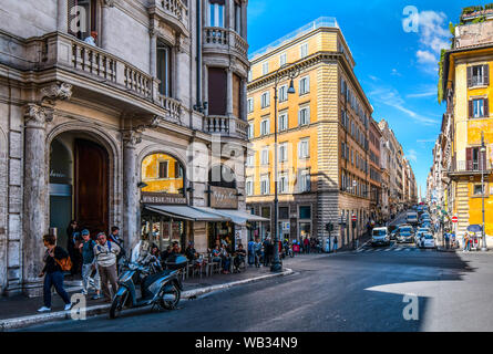 Tourists enjoy lunch at a sidewalk cafe on a busy intersection in the historic center of Rome, Italy. - Stock Photo